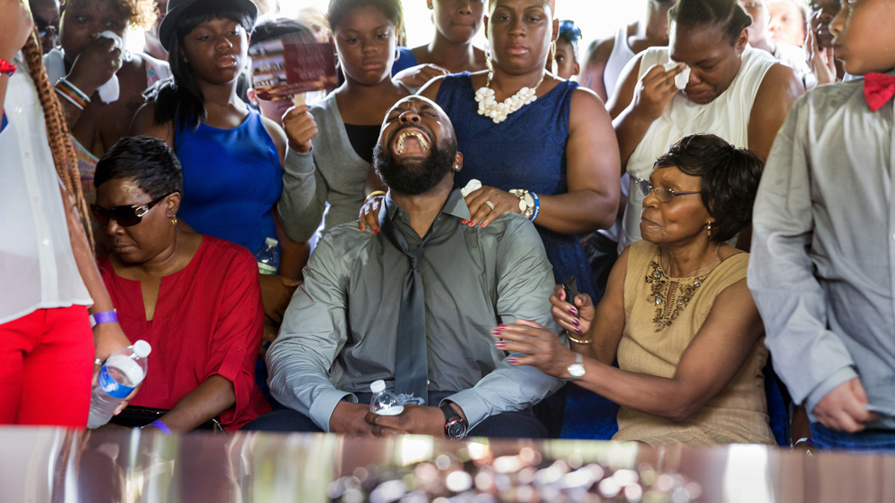 Michael Brown Sr., yells out as the casket is lowered during the funeral service for his son Michael Brown in Normandy, Mo., Monday, Aug. 25, 2014. Hundreds of people gathered to say goodbye to Michael Brown, the 18-year-old shot and killed Aug. 9 in a confrontation with a police officer that fueled almost two weeks of street protests. (AP Photo/New York Times, Richard Perry, Pool)