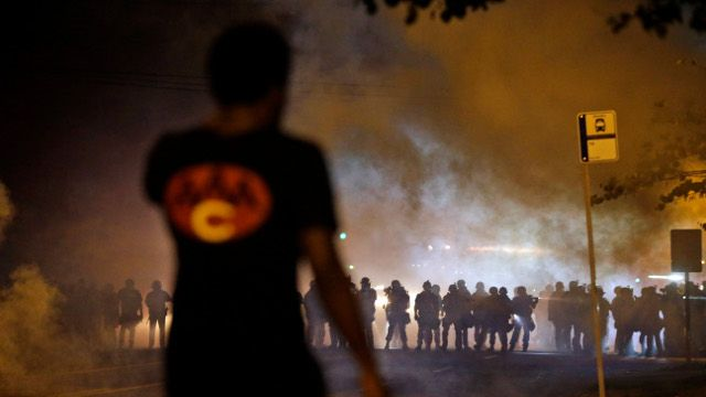 A man watches as police walk through a cloud of smoke during a clash with protesters Wednesday, Aug. 13, 2014, in Ferguson, Mo. Protests in the St. Louis suburb rocked by racial unrest since a white police officer shot an unarmed black teenager to death turned violent Wednesday night, with people lobbing Molotov cocktails at police who responded with smoke bombs and tear gas to disperse the crowd. (AP Photo/Jeff Roberson)