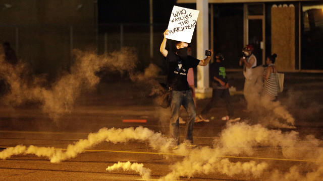 A protester stands in the street after police fired tear gas to disperse a crowd Sunday, Aug. 17, 2014, during a protest for Michael Brown, who was killed by a police officer last Saturday in Ferguson, Mo. (AP Photo/Charlie Riedel)