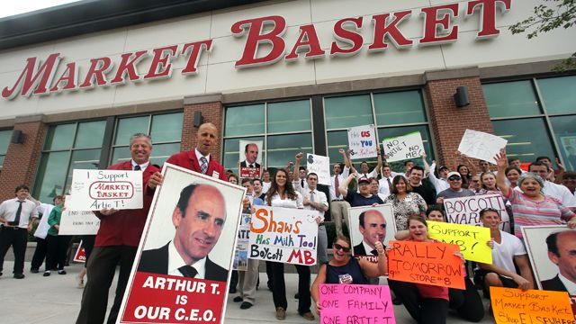 """Market Basket assistant managers Mike Forsyth, left, and John Surprenant, second from left, hold signs while posing with employees in Haverhill, Mass., Thursday, July 24, 2014, in a show of support for """"Artie T."""" Arthur T. Demoulas, the former chief executive of the Market Basket supermarket chain whose ouster has led to employee protests, customer boycotts and empty shelves, says he wants to buy the entire company. (AP Photo)"""