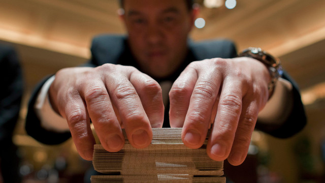 Baccarat dealer Ramiro Nepomuceno, right, shuffles cards while preparing a table for play at the MGM Hotel and Casino, in Las Vegas.  (AP Photo/Julie Jacobson, File)