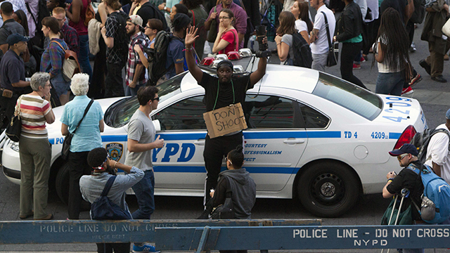 Holding a camera and wearing a 'Don'™t Shoot'€ sign, Antoine Wallace raises his hands while leaning against a New York City police car during a protest march in New York, Thursday, Aug. 14, 2014. (AP Photo/Michael R. Sisak)