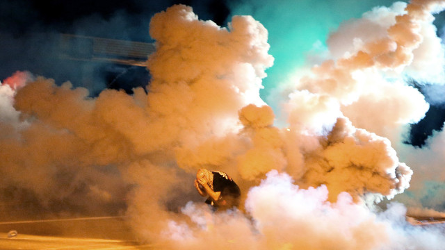 A protester takes shelter from smoke billowing around him Wednesday, Aug. 13, 2014, in Ferguson, Mo. Protests in the St. Louis suburb rocked by racial unrest since a white police officer shot an unarmed black teenager to death turned violent Wednesday night. (AP Photo/St. Louis Post-Dispatch, David Carson)