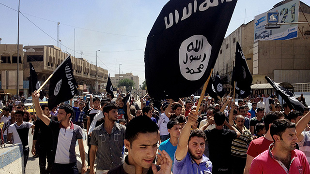 Demonstrators chant pro-al-Qaida-inspired Islamic State of Iraq and the Levant (ISIL) as they carry al-Qaida flags in front of the provincial government headquarters in Mosul, 225 miles (360 kilometers) northwest of Baghdad, Iraq, Monday, June 16, 2014. (AP Photo)