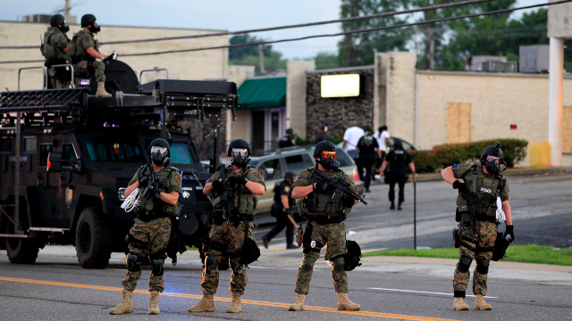 Police wearing riot gear try to disperse a crowd Monday, Aug. 11, 2014, in Ferguson, Mo. Authorities in Ferguson used tear gas and rubber bullets to try to disperse a large crowd Monday night. (AP Photo/Jeff Roberson)
