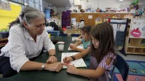 Kindergarten teacher Amy Weisberg helps students in her classroom (AP Photo/Nick Ut)