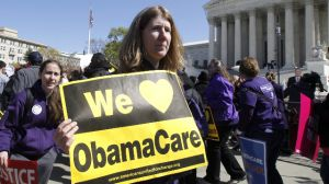 """Holding a sign saying """"We Love ObamaCare"""" supporters of health care reform rally in front of the Supreme Court in Washington, Tuesday, March 27, 2012, as the court continued hearing arguments on the health care law signed by President Barack Obama.  (AP Photo/Charles Dharapak)"""
