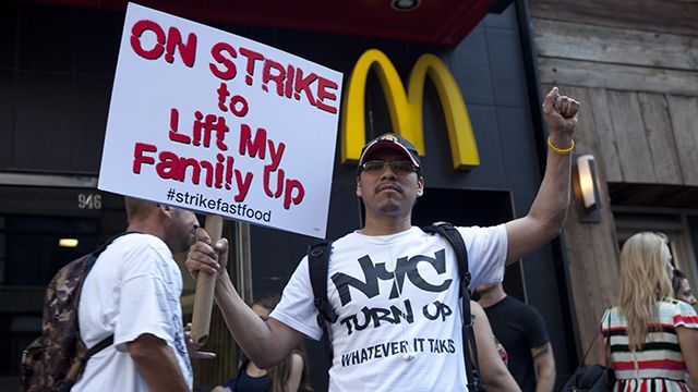 """On September 4, 2014, a protester holding a sign that says """"On Strike to Lift My Family Up"""" was in front of McDonald restaurant near Columbus Circle. In New York City, 21 fast food workers were arrested that day in an organized nationwide strike to demand $15-an-hour and a union. (Photo: Charina Nadura/ Moyers & Company)"""