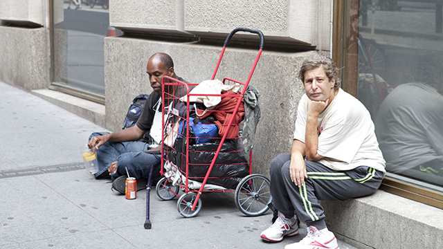 Homeless people on Wall St. area ask for change from people walking by. (Credit: Charina Nadura/Moyers & Company)