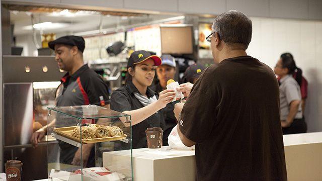 A worker in McDonald near Wall St. hands a hash brown to a customer. (Credit: Charina Nadura)