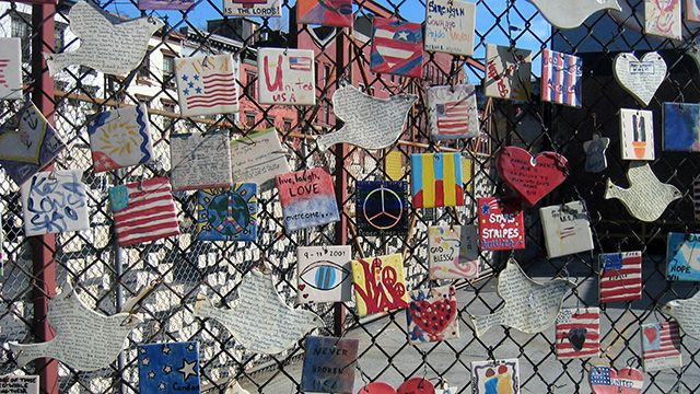 Tiles for America began on September 12, 2001. In the aftermath of the tragedy, crowds gathered in large numbers in front of Saint Vincent's Hospital, located at the corner of 7th Avenue and 11th Street. This was the hospital that was prepared to receive the thousands of survivors that many people were hopeful they would be. Lorrie Veasey, owner of OUR NAME IS MUD, also located on 11th Street, began to create what she hoped would be an inspiration to recovering victims. From raw clay she fashioned approximately 5000 small angels and American flags, which she and friends attached to a fence that faced the hospital on September 14. The angels and flags were attached with ribbon, and before two weeks had passed, most of them had been removed from the fence. (Photo: Wally Gobetz/flickr CC 2.0)