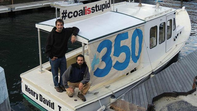 Ken Ward (left) and Jay O'Hara on the boat they used to block the delivery of 40,000 tons of coal to a power plant in Somerset. (Photo: 350Mass)
