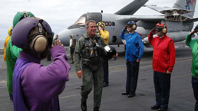 President George W. Bush on the Abraham Lincoln being saluted by the flight deck crew. (Image: US Navy/ Photographer's Mate 3rd Class Tyler J. Clements.)