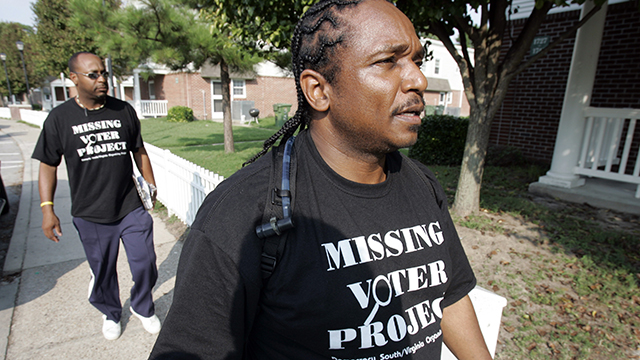 James Bailey, who created the 10,000 voter project, front, walks through Oakleaf Forest housing project along with Tony Taylor in Norfolk, Virginia, Tuesday, July 29, 2008. The two were knocking on doors asking residents to register to vote, and making a special effort to register felons.