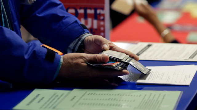 In this Wednesday, Feb. 26, 2014 photo, a voter shows his photo identification to an election official at an early voting polling site, in Austin, Texas.  (AP Photo/Eric Gay)