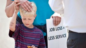Marie Mulder holds her son, Jonah Spoelma, 6, while protesting in front of the Grand Rapids Public Library Tuesday, May 20, 2014 in Grand Rapids, Mich. Library workers in Grand Rapids say plans to cut 18 jobs this summer will mean less service for area residents.  (AP Photo/The Grand Rapids Press, Cory Morse)