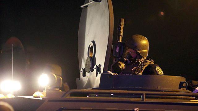 A member of the Missouri Highway Patrol is seen atop an armored personnel carrier Monday, Aug. 18, 2014, in Ferguson, Mo. The Aug. 9 shooting of Michael Brown by police has touched off rancorous protests in Ferguson, a St. Louis suburb where police have used riot gear and tear gas. (AP Photo/Jeff Roberson)