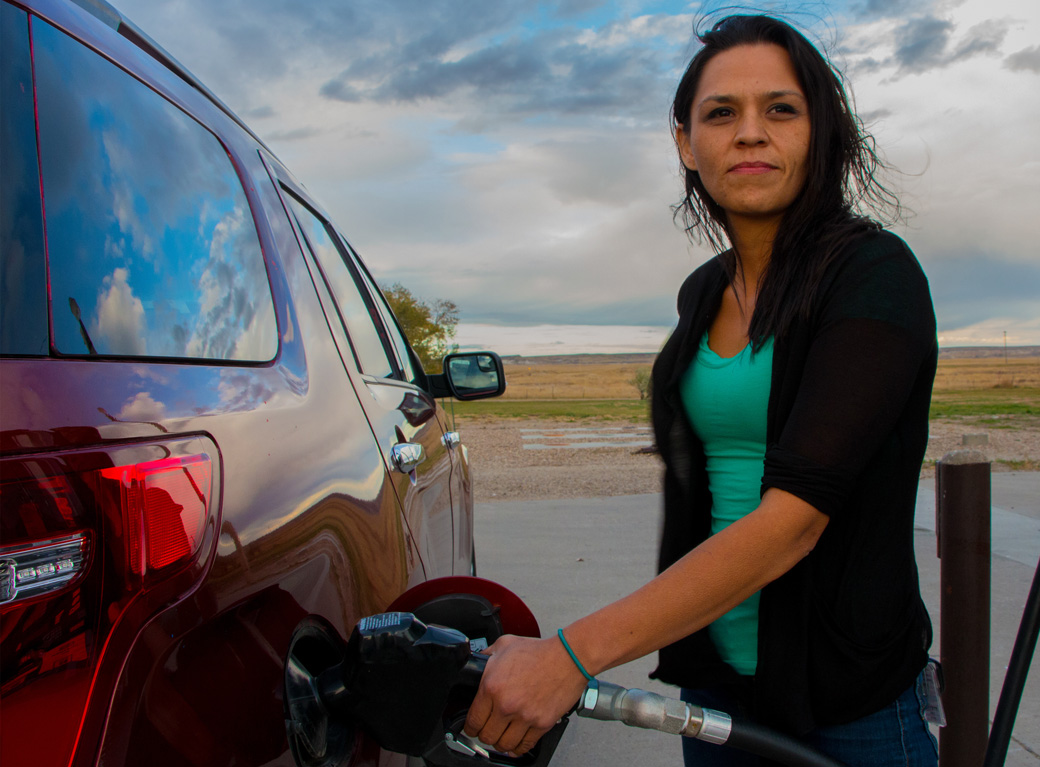 Get-out-the-vote field coordinator Donna Semans, Rosebud Sioux, gases up her vehicle in Sharps Corner, on the north end of Pine Ridge Indian Reservation. On Pine Ridge, families may share cars, and money for gas is scarce, so GOTV is essential in helping people get to the polls.  (Credit: Jesse Short Bull)