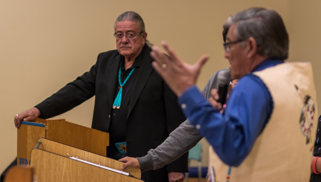 On November 4, 2014, Pine Ridge voters will select tribal officials, as well as county, state and national ones. The tribal candidates debated on October 28 at Red Cloud Indian School, north of Pine Ridge Village. Here current tribal president, Bryan Brewer, listened as his opponent, former president John Yellow Bird Steele, answered a question. Drawn up by students, the questions asked what candidates would do to solve the reservation's dire need for housing, how they'd make the government more responsive to the people and more. (Credit: Jesse  Short Bull)