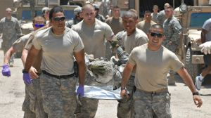 Soldiers with C Company, 1st Battalion, 26th Infantry Regiment, at forward operating base Apache in eastern Baghdad carry injured soldiers to the medical center at the base in eastern Baghdad after an IED destroyed a Bradley fighting vehicle killing five U.S. soldiers and an Iraqi interpreter June 21, 2007 in the Adhamiyah neighborhood of Baghdad, Iraq. (AP Photo/Army Times, Rick Kozak)