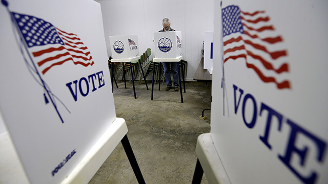 Bow Stanley, from Silver Lake, Kansas, votes at the Prairie Home Cemetery building, Tuesday, Nov. 4, 2014, in Topeka, Kansas. (Photo by Charlie Riedel/AP)