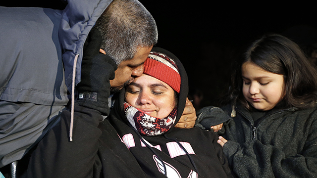 Carlos Zuniga, left, kisses his wife Lenka Zuniga, with their daughter Fiorella Zuniga, all from Peru, during a demonstration in front of the White House in Washington, Thursday, Nov. 20, 2014. Lenka Zuniga has been on an 18 day hunger strike. President Barack Obama announced executive actions on immigration during a nationally televised address. (AP Photo/Alex Brandon)