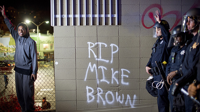 A protester stands near a wall with a graffiti and police officers in Oakland, California, on Monday, Nov. 24, 2014, after the announcement that a grand jury decided not to indict Ferguson police officer Darren Wilson in the fatal shooting of Michael Brown, an unarmed 18-year-old. (AP Photo/Noah Berger)