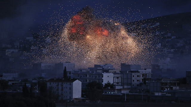 In Oct. 20, 2014, thick smoke and flames from an airstrike by the US -led coalition rise in Kobani, Syria, as seen from a hilltop on the outskirts of Suruc, at the Turkey-Syria border. The airstrike is part of the 'Operation Inherent Resolve' by the US government to diminish the jihadist group ISIS. (AP Photo/Lefteris Pitarakis, File)