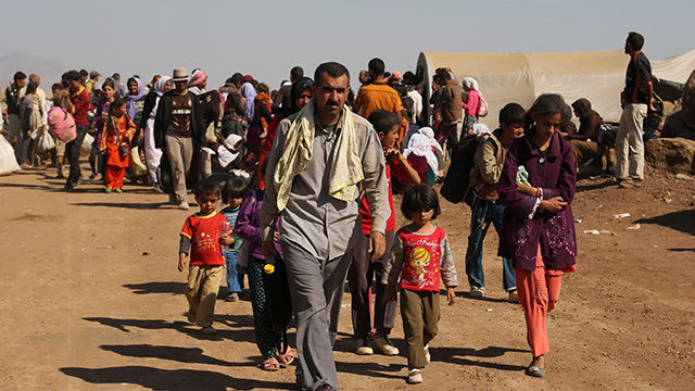 On Aug. 12, 2014, displaced Iraqis from the Yazidi community arrive at Nowruz camp, in Derike, Syria. Islamic State militiamen backed by tanks defiantly marched on in Syria, capturing 21 Kurdish villages even as the international community strains to assemble a coalition that might destroy them. (AP Photo/ Khalid Mohammed, File)