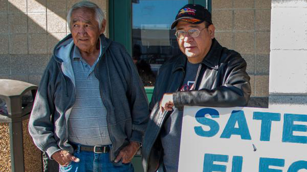 GOTV driver Cedric Goodman Jr. (right) delivers elder Timothy He Crow to the polls. (Credit: Jesse Short Bull)