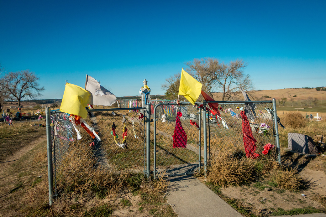 Prayer flags adorn the fence surrounding the mass grave at Wounded Knee. The burial holds the remains of Lakotas, many of them women and children, gunned down by Seventh Cavalry soldiers in December 1890. More prayer flags flutter from contemporary graves surrounding the historic site.