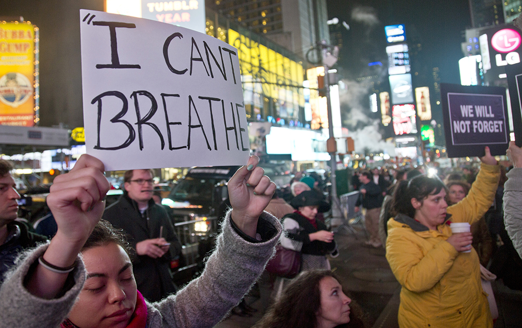 Protesters in Times Square carry signs in reaction to a non indictment against a police officer in the death of Eric Garner, Wednesday Dec. 3, 2014 in New York.  (AP Photo/Bebeto Matthews)