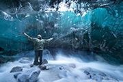 Adventurer photographs cave below a glacier, Juneau, Alaska - Au