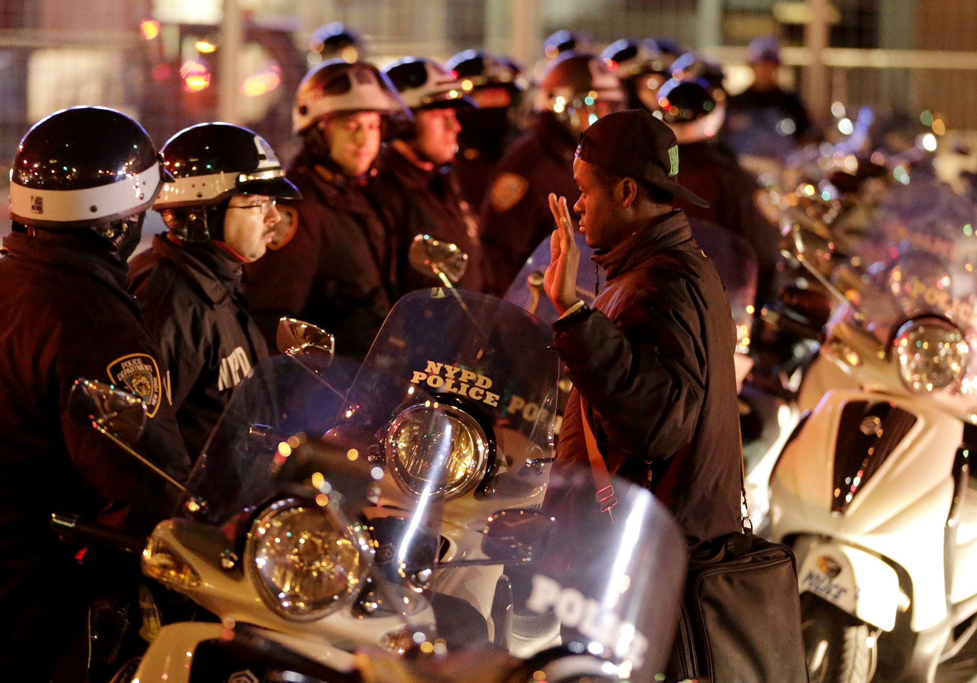 A man stands with his hands raised in front of a line of police officers during a protest after it was announced that the New York City police officer involved in the death of Eric Garner was not indicted, Wednesday, Dec. 3, 2014, in New York. (AP Photo/Julio Cortez)