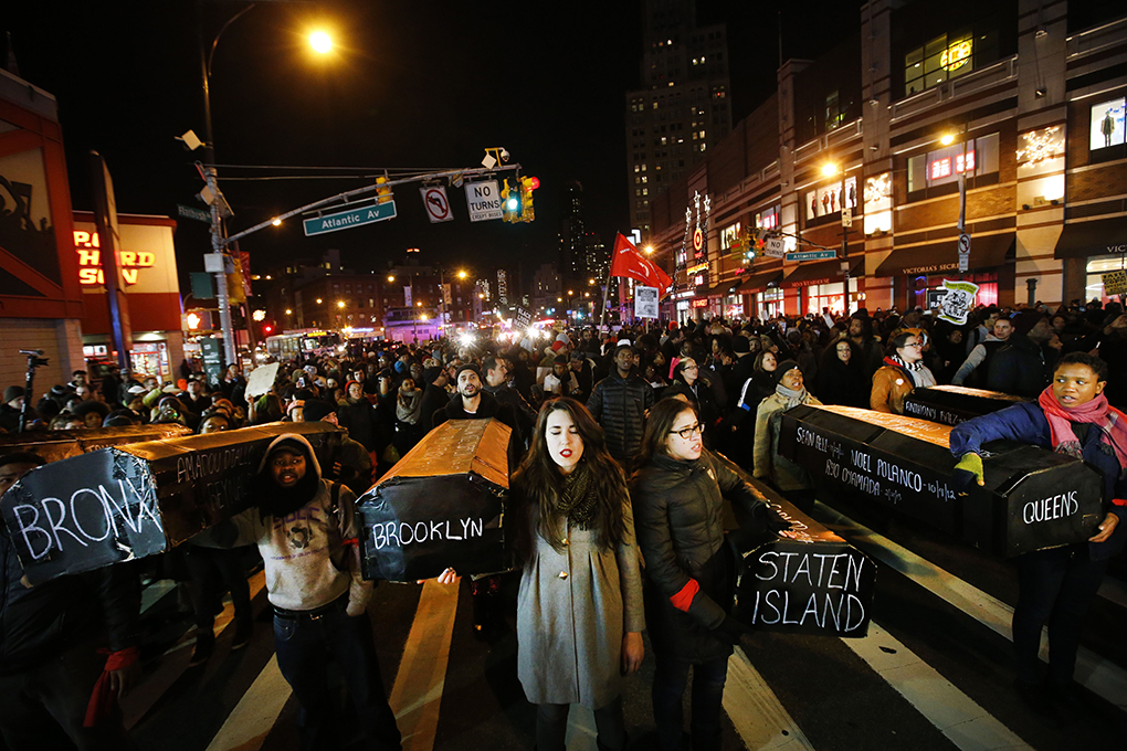 Protesters rallying against a grand jury's decision not to indict the police officer involved in the death of Eric Garner sing as they carry a collection of mock coffins bearing the names of victims of fatal police encounters at the intersection of Flatbush Avenue and Atlantic Avenue near the Barclays Center, Thursday, Dec. 4, 2014, in the Brooklyn borough of New York.  A grand jury cleared a white New York City police officer Wednesday in the videotaped chokehold death of Garner, an unarmed black man, who had been stopped on suspicion of selling loose, untaxed cigarettes. (AP Photo/Jason DeCrow)