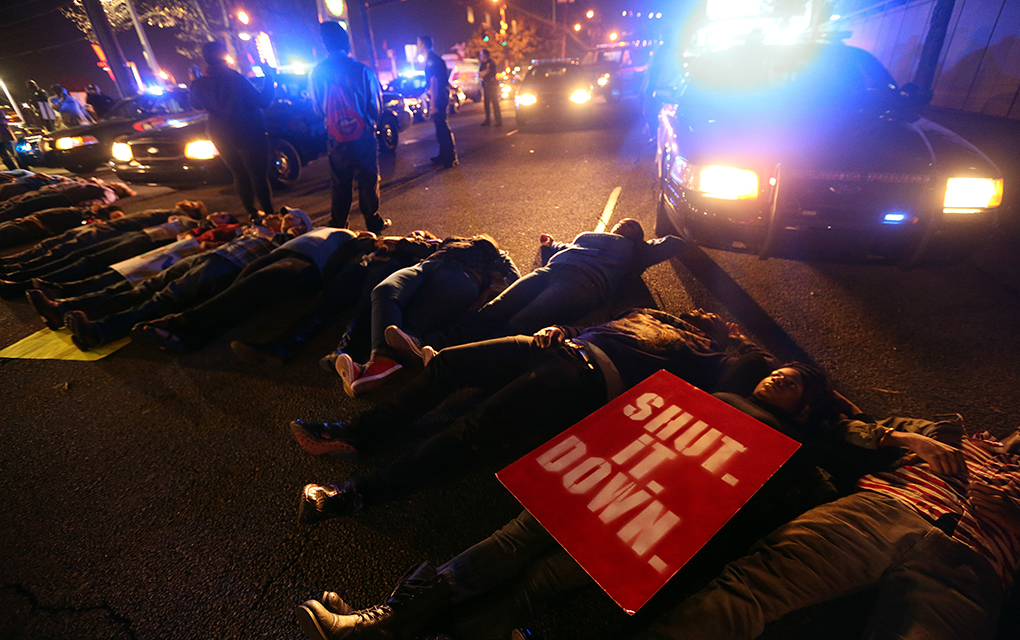 Protesters lie down and block Spring Street in Downtown Atlanta on Wednesday night December 3, 2014 while protesting the New York City grand jury's decision to clear a white police officer who killed an unarmed black man.   (AP Photo/Atlanta Journal-Constitution, Ben Gray)