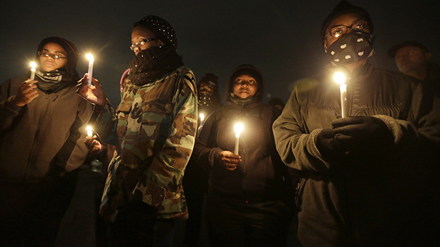 Young women attend a candlelight vigil for victims of gun violence Friday, Oct. 10, 2014, in Ferguson, Missouri. (AP Photo/Charles Rex Arbogast)