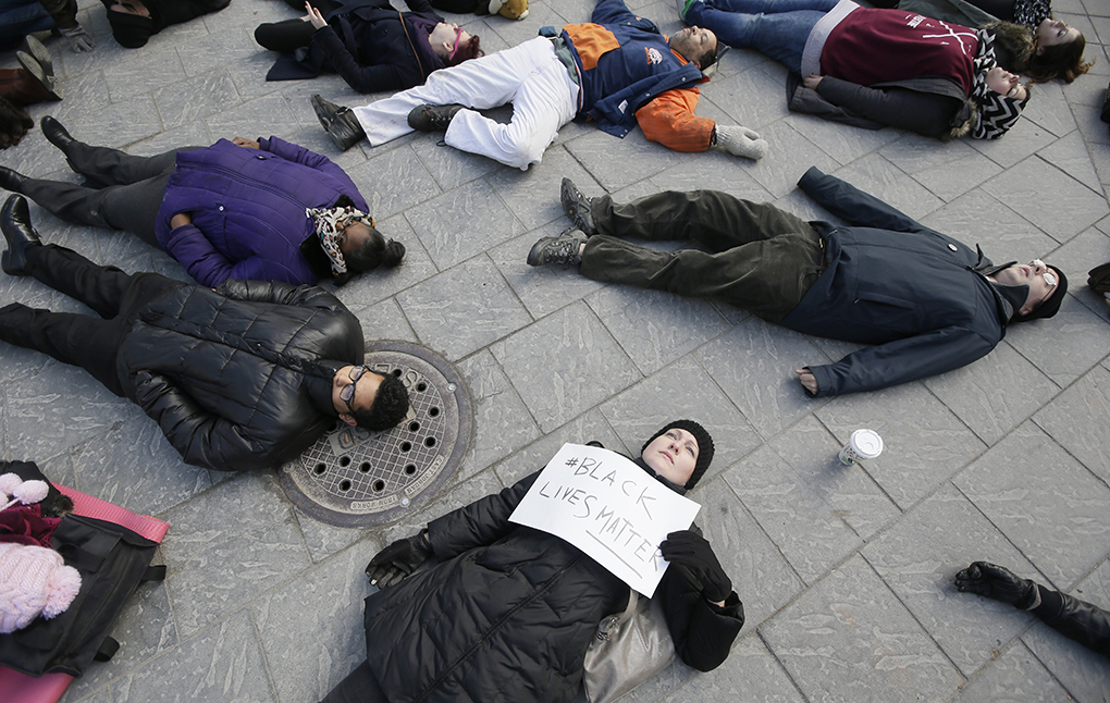 Katie McGowan holds a sign as she and other demonstrators lie on the ground at Campus Martius in downtown Detroit, Thursday, Dec. 4, 2014 protesting the non indictment of a white New York police officer in the choking death of Eric Garner. (AP Photo/Carlos Osorio)