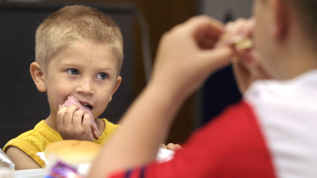 Christian Kellogg, 6, left, and his brother Anthony Kellogg, 9, eat lunch at King Elementary School in Des Moines, Iowa, Tuesday, July 27, 2004. The school offer free lunches to neighborhood children as part of the federal government's free and reduced-price lunch program for low-income children. (AP Photo/J. Mark Kegans)