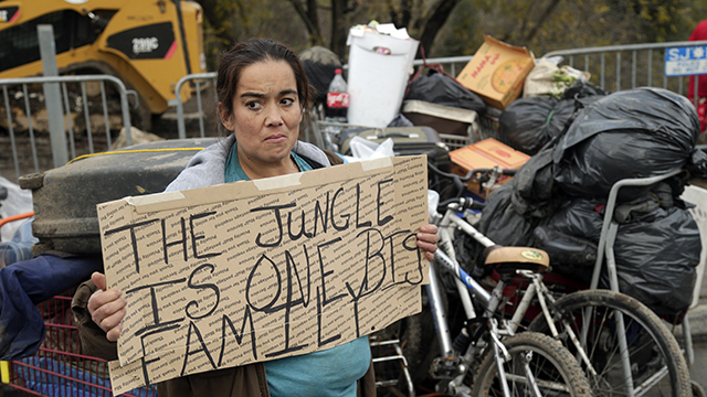 Yolanda Gutierrez, a 2-year resident of  a homeless encampment known as The Jungle, holds a sign in protest Thursday, Dec. 4, 2014, in San Jose, California. Police and social-workers began clearing away one of the nation's largest homeless encampments, a cluster of flimsy tents and plywood shelters that once housed more than 200 people in the heart of California's wealthy Silicon Valley. (AP Photo/Marcio Jose Sanchez)