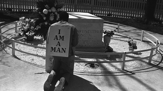 "A striking Atlanta sanitation worker kneels at the grave of Dr. Martin Luther King Jr. after a rally by Southern Christian Leadership Conference supporting the strike in Atlanta on April 4, 1970. King was killed in Memphis, Tenn., two years ago while supporting a sanitation workers' strike there. The picket signs reading ""I Am A Man"