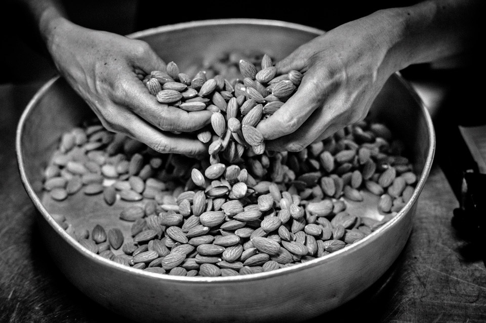 A worker sorts almonds at a processing plant near Los Banos in California's Central Valley. Photo by Matt Black.