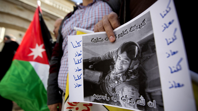 A Palestinian hold a poster with a picture of slain Jordanian pilot, Lt. Muath al-Kaseasbeh during a protest in front of the Jordanian embassy, in the West Bank City of Ramallah, Wednesday, Feb. 4, 2015. (AP Photo/Majdi Mohammed)