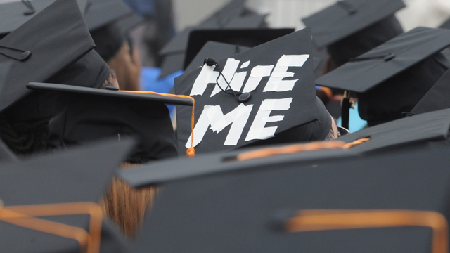 """A cap worn by graduate Paul Szeto, of Cambridge, Mass., reads, """"hire me"""" as graduates listens to speakers during University of Massachusetts -Boston commencement, Friday, May 29, 2009 in Boston. Job prospects for college graduates are not promising in this time of financial turmoil. (AP Photo/Lisa Poole)"""
