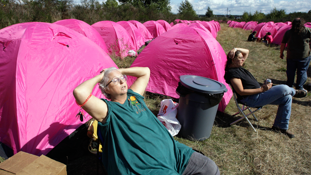 Catharine Fletcher suns herself in front of one of over a hundred brilliant pink tents newly set-up as a shelter for homeless people Monday, Sept. 22, 2008, in Seattle. Homeless advocates in Seattle set up a new camp early Monday that they're calling Nickelsville after Mayor Greg Nickels to demonstrate the need for more homeless shelters in the city. Fletcher is no longer homeless, but was helping out at the encampment. (AP Photo/Elaine Thompson)