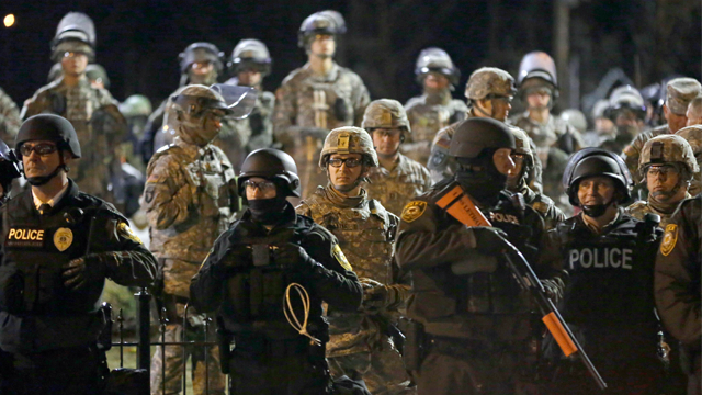 Police and Missouri National Guardsmen stand guard against protesters in front of Ferguson Police Department on Friday, Nov. 28, 2014, in Ferguson, Missouri. (AP Photo/Jeff Roberson)
