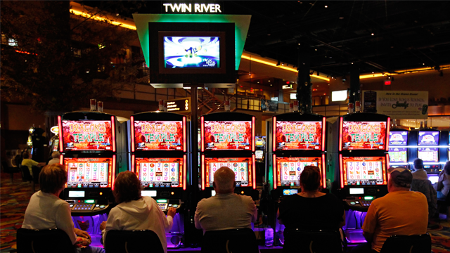 (Patrons play slot machines at the Twin River Casino, in Lincoln, Rhode Island in 2011. Rhode Island voters voted to allow Twin River to offer table games in 2012. A subsidiary of Twin River spent millions on a 2014 ballot measure to expand gaming in Colorado. Photo by Steven Senne/AP)