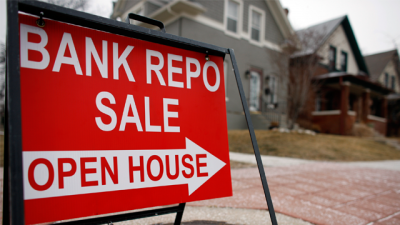 A bank repossession sign points the way to an existing home on the market in south Denver on Sunday, Jan. 25, 2009. (AP Photo/David Zalubowski)