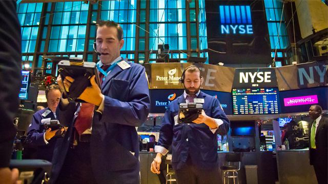 Traders work from handheld computers as they review stock information at the New York Stock Exchange during early trading, Monday, Dec. 15, 2014, in New York. U.S. stocks opened broadly higher Monday following the biggest weekly losses in two and a half years. (AP Photo/Bebeto Matthews)