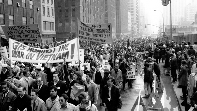 """Thousands of anti-Vietnam war protesters march along the Avenue of the America's on 6th Avenue in New York City on April 5, 1969. Many of the protesters wore black arm bands bearing the number """"33,000,"""" referring to the American deaths in Vietnam. (AP Photo)"""